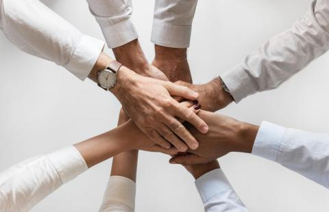 Eight people holding their hands on top of one another.